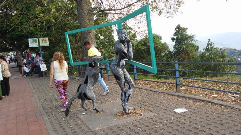 Escultura de hombre y perro mirando el paisaje