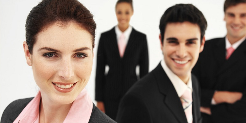 Front view portrait of four business executives smiling --- Image by © Royalty-Free/Corbis