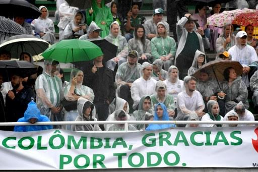 """People attend under the rain the funeral of the members of the Chapecoense Real football club team killed in a plane crash in Colombia, at the stadium in  Chapeco, Santa Catarina, southern Brazil, on December 3, 2016. The banner reads """"Thanks for Everything, Colombia"""". The bodies of 50 players, coaches and staff from a Brazilian football team tragically wiped out in a plane crash in Colombia arrived home Saturday for a massive funeral. / AFP PHOTO / Nelson Almeida"""