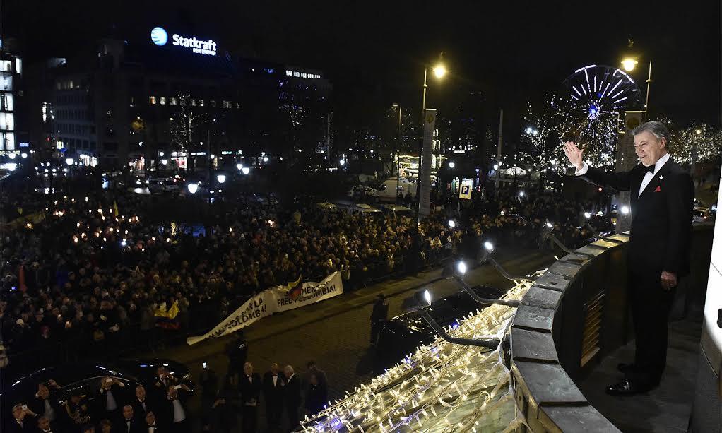 El Presidente Juan Manuel Santos saluda desde el balcón del Grand Hotel la marcha de las antorchas, con la que el pueblo Noruego lo agasaja,  tras recibir el Premio Nobel de Paz 2016.